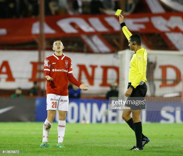 Referee Wagner do Nascimento Magalhaes shows a yellow card to Norberto Briasco of Huracan during a first leg match between Huracan and Libertad as...