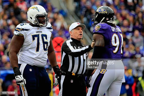 Referee Walt Anderson separates tackle DJ Fluker of the San Diego Chargers and outside linebacker Courtney Upshaw of the Baltimore Ravens in the...