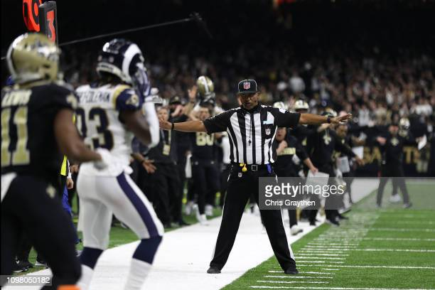 A referee watches as Tommylee Lewis of the New Orleans Saints drops a pass broken up by Nickell RobeyColeman of the Los Angeles Rams during the...