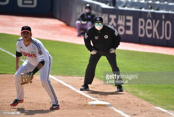 A referee wearing a face mask looks on at the first base during a preseason baseball game between Seoulbased Doosan Bears and LG Twins at Jamsil...