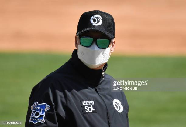 A referee wearing a face mask looks on during a preseason baseball game between Seoulbased Doosan Bears and LG Twins at Jamsil stadium in Seoul on...