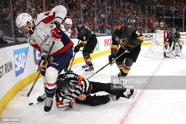Referee Wes McCauley gets tripped up as Tom Wilson of the Washington Capitals and Deryk Engelland of the Vegas Golden Knights battle for the puck...