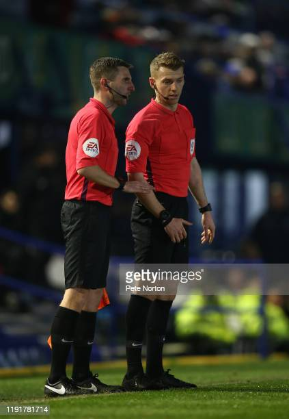 Referee Will Finnie talks to his assistant Michael Webb during the Leasingcom Trophy match between Portsmouth and Northampton Town at Fratton Park on...