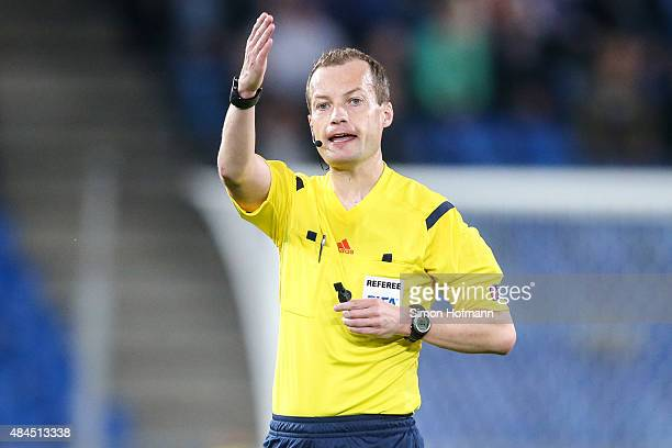 Referee William Collum gestures during the UEFA Champions League qualifying round play off first leg match between FC Basel and Maccabi Tel Aviv at...