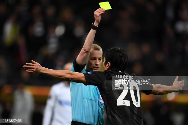 Referee William Collum of Scotland shows an yellow card to Makoto Hasebe of Eintracht Frankfurt during the UEFA Europa League Round of 16 First Leg...
