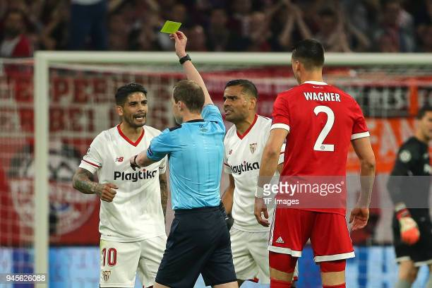 Referee William Collum shows a yellow card to Ever Banega of Sevilla during the UEFA Champions League quarter final second leg match between Bayern...