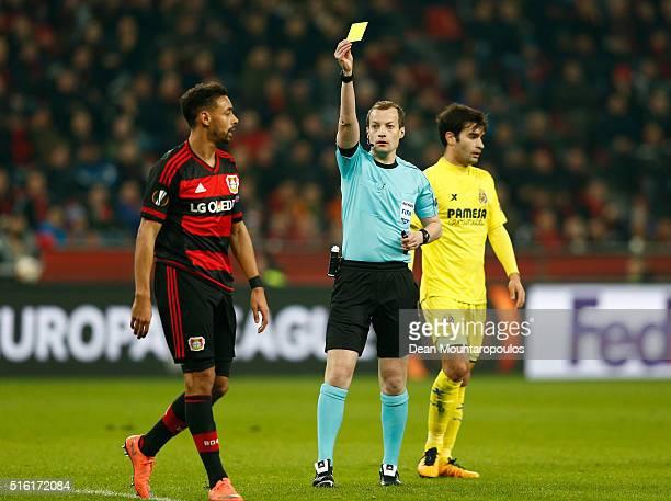 Referee William Collum shows a yellow card to Karim Bellarabi of Bayer Leverkusen during the UEFA Europa League round of 16, second leg match between...
