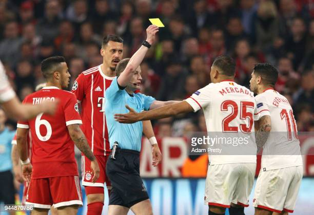 Referee William Collum shows Ever Banega of Sevilla a yellow card during the UEFA Champions League Quarter Final Second Leg match between Bayern...