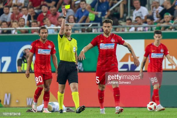 Referee William Collum shows Mihai Pintilii of FCSB yellow card during the - UEFA Europa League Play Off: First Leg match between Rapid v FCSB...