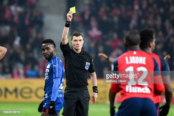 Referee Willy Delajod gives a yellow card to John Mendoza of Amiens during the Ligue 1 match between Lille and Amiens at Stade Pierre Mauroy on...