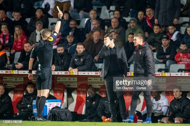 Referee Willy Delajod shows the yellow card towards the Rennes bench as Julien Stephan manager of Rennes holds his head in his hands on the sideline...