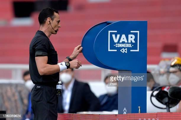 Referee Wilmar Roldan checks the VAR during a match between Ecuador and Uruguay as part of South American Qualifiers for Qatar 2022 at Rodrigo Paz...