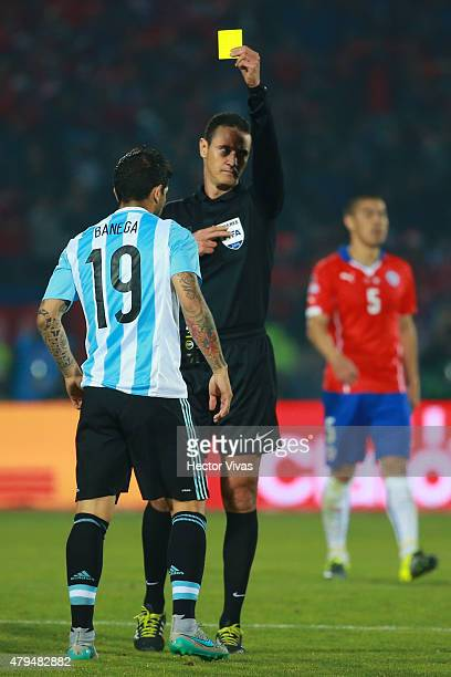 Referee Wilmar Roldan shows a yellow card to Ever Banega of Argentina during the 2015 Copa America Chile Final match between Chile and Argentina at...