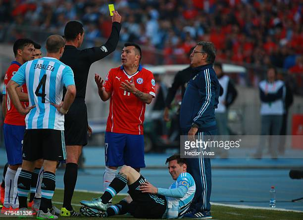 Referee Wilmar Roldan shows a yellow card to Gary Medel of Chile during the 2015 Copa America Chile Final match between Chile and Argentina at...