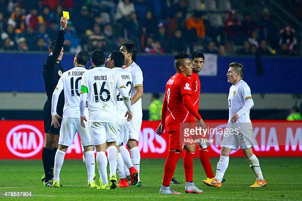 Referee Wilmar Roldan shows a yellow card to Pablo Escobar of Bolivia during the 2015 Copa America Chile quarter final match between Peru and Bolivia...