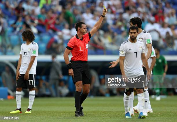 Referee Wilmar Roldan shows Ali Gabr of Egypt a yellow card during the 2018 FIFA World Cup Russia group A match between Saudia Arabia and Egypt at...
