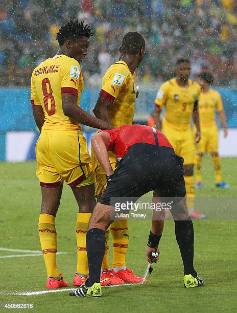 Referee Wilmar Roldan sprays a temporary line for a free kick as Benjamin Moukandjo and Enoh Eyong of Cameroon form a wall during the 2014 FIFA World...