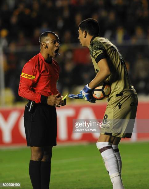Referee Wilton Pereira Sampaio argues with Esteban Andrada of Lanus after showing him a yellow card during a first leg match between The Strongest...