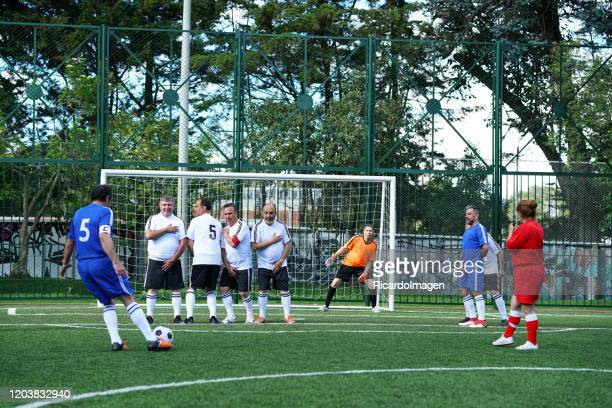 referee woman dressed in red uniform is in the middle of a football match watching as one of the blue team players with the number 5 in his shirt takes a free kick while the white team players make a barrier to prevent the goal - soccer competition stock pictures, royalty-free photos & images