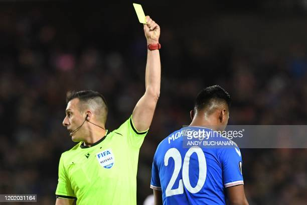 Referee Xavier Estrada Fernandez shows a yellow card to Rangers' Colombian striker Alfredo Morelos during the UEFA Europa League round of 32 first...