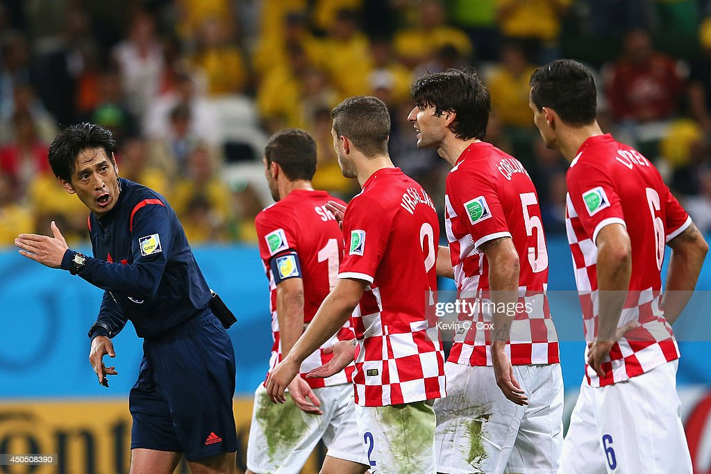 Referee Yuichi Nishimura is pursued by Darijo Srna, Sime Vrsaljko, Vedran Corluka and Dejan Lovren of Croatia after awarding a penalty kick and giving Lovren a yellow card in the second half during the 2014 FIFA World Cup Brazil Group A match between Brazil and Croatia at Arena de Sao Paulo on June 12, 2014 in Sao Paulo, Brazil.