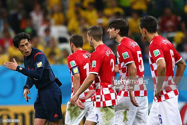 Referee Yuichi Nishimura is pursued by Darijo Srna Sime Vrsaljko Vedran Corluka and Dejan Lovren of Croatia after awarding a penalty kick and giving...
