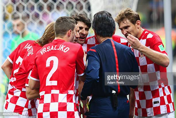 Referee Yuichi Nishimura is surrounded by Croatia players after awarding a penalty kick in the second half during the 2014 FIFA World Cup Brazil...