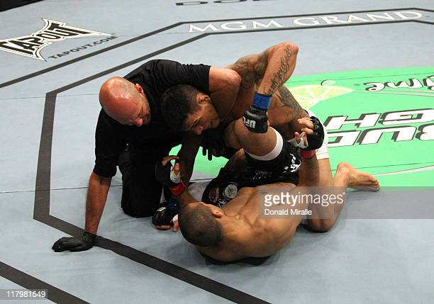 Referee Yves Lavigne pulls Rafael Dos Anjos off George Sotiropoulos awarding the victory to Dos Anjos by knockout in a lightweight bout at UFC 132 at...