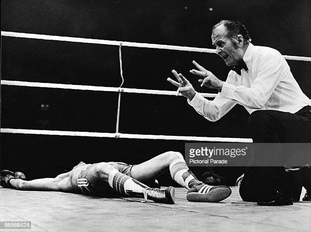 A refereee administers the count over English professional boxer Dave 'Boy' Green who lies flat on his back after being knocked out in the eleventh...