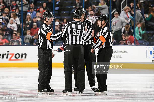 NHL referees and linemen Wes McCauley Steve Barton Derek Amell and Brian Pochmara gather at center ice before the start of an NHL game between the...