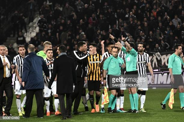 Referees and players stand in confusion on the pitch during incidents following the referee's decision to disallow PAOK an injurytime goal on March...