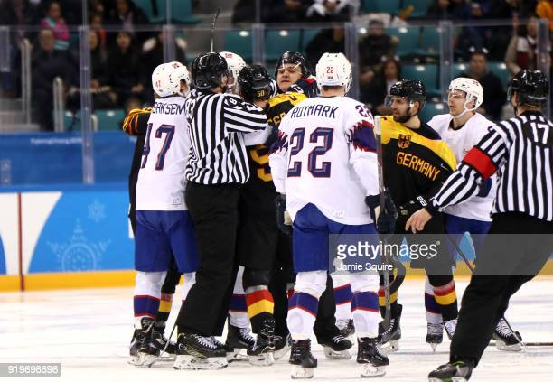 Referees attempt to separate Patrick Hager of Germany and Alexander Bonsaksen of Norway in the second period during the Men's Ice Hockey Preliminary...