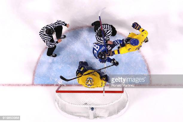 Referees attempt to separate Patrik Hersley of Sweden and VeliMatti Savinainen of Finland in the first period during the Men's Ice Hockey Preliminary...