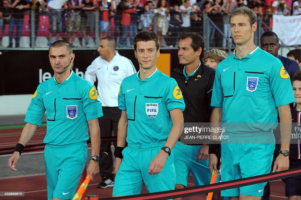 Referees Benoit Bastien (C), Frederic Haquette (L) and Christophe Mouysset arrive on the pitch for the French L1 football match between Evian Thonon Gaillard (ETGFC) and Paris Saint-Germain (PSG) on August 22, 2014 at the Parc des Sport in Annecy, southeastern France.