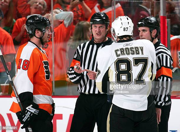 Referees Brad Watson and Chris Rooney explain penalties to captains Mike Richards of the Philadelphia Flyers and Sidney Crosby of the Pittsburgh...