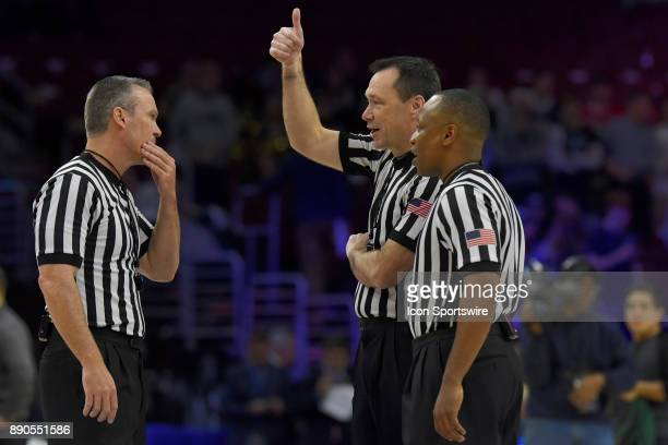 Referees chat mid court during a time out during the college basketball game between the La Salle Explorers and the Villanova Wildcats on December 10...