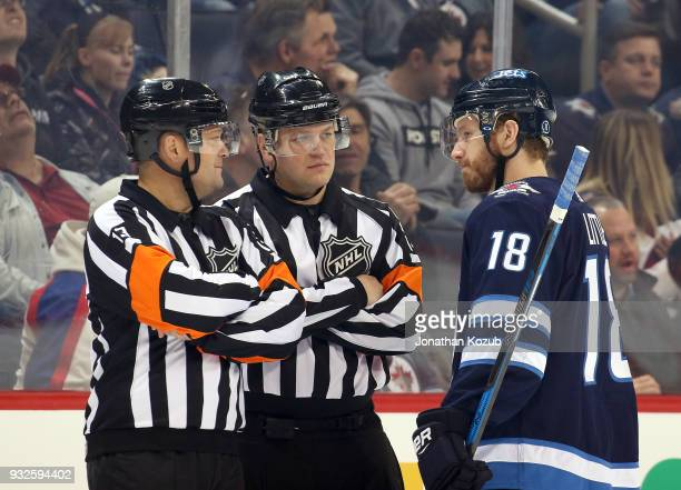 Referees Dan O'Halloran and Trevor Hanson keep their eye on Bryan Little of the Winnipeg Jets during a first period stoppage in play against the...