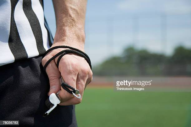 Referee's hand holding whistle