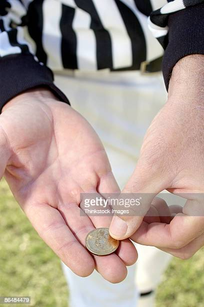 Referees hands with coin