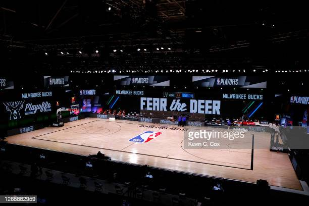 Referees huddle on an empty court at game time of a scheduled game between the Milwaukee Bucks and the Orlando Magic for Game Five of the Eastern...
