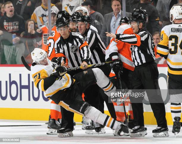 Referees Jean Hebert and Tim Peel react to Evgeni Malkin of the Pittsburgh Penguins during a scrum against the Philadelphia Flyers on March 7 2018 at...