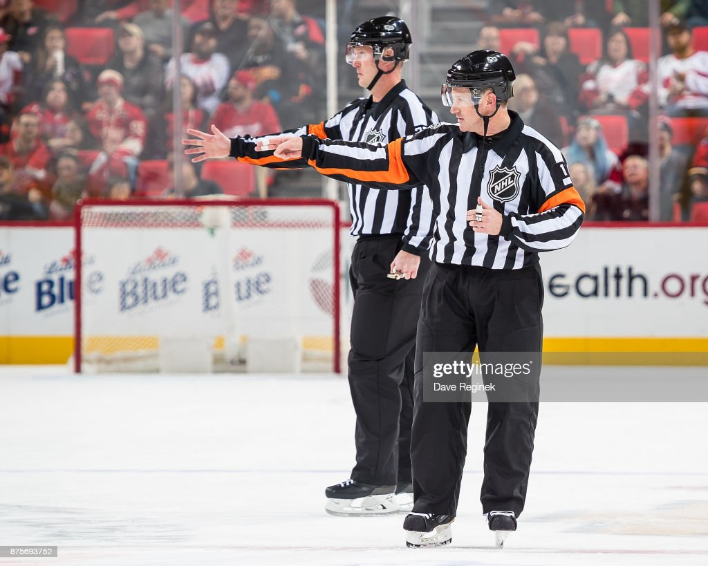 Referee's Kelly Sutherland #11 and Kevin Pollock #33 signal a good goal after a video review during an NHL game between the Detroit Red Wings and the Calgary Flames at Little Caesars Arena on November 15, 2017 in Detroit, Michigan. The Red Wings defeated the Flames 8-2.