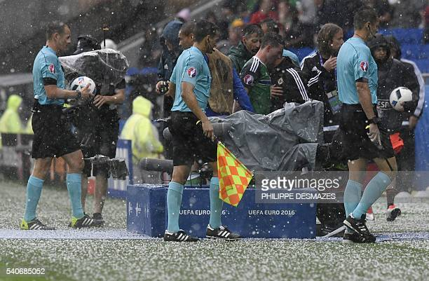 Referees leave the pitch during a hailstorm during the Euro 2016 group C football match between Ukraine and Northern Ireland at the Parc Olympique...