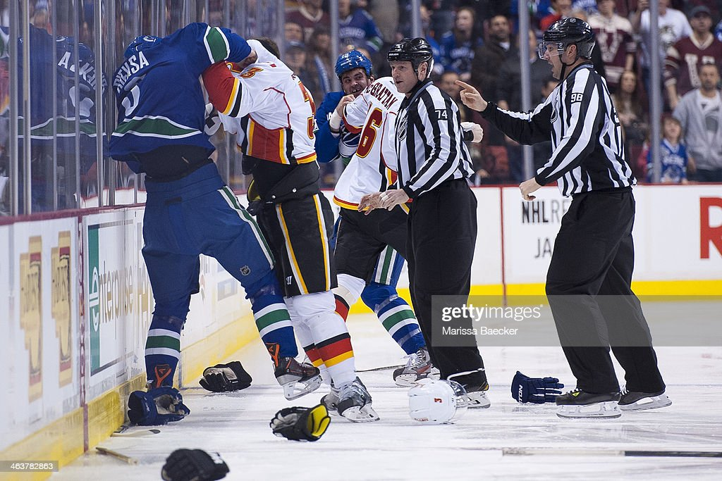 Referees look on as Kevin Bieksa #3 of the Vancouver Canucks fights Ladislav Smid #3 of the Calgary Flames as Tom Sestito #29 of the Vancouver Canucks takes on Brian McGrattan #16 of the Calgary Flames on January 18, 2014 at Rogers Arena in Vancouver, British Columbia, Canada.