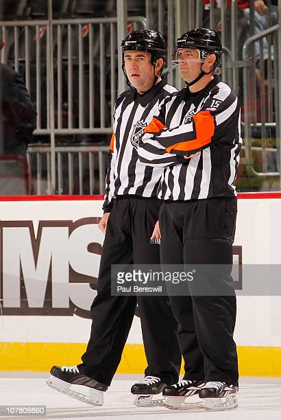 Referees Marc Joannette and Stephane Auger talk during a timeout in an NHL hockey game between the Toronto Maple Leafs and New Jersey Devils at the...