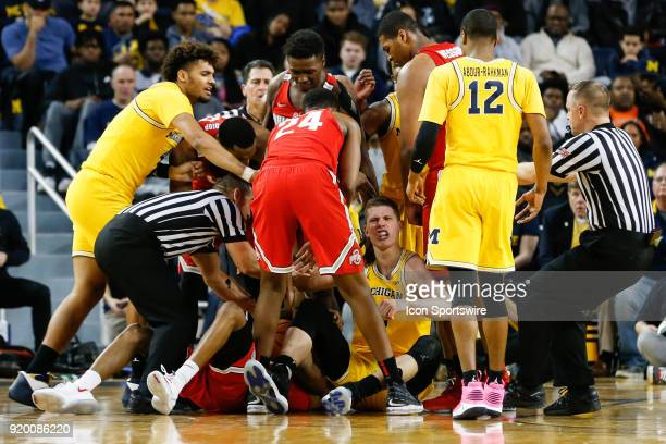 Referees pull Michigan and Ohio State players out of a scrum while Michigan Wolverines forward Moritz Wagner has words with Ohio State Buckeyes...