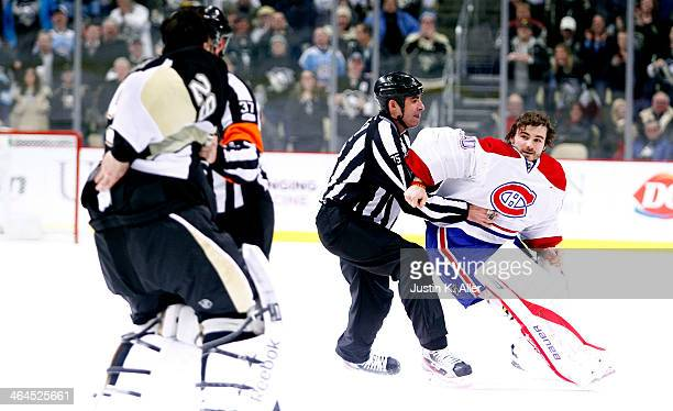 Referees restrain goaltenders MarcAndre Fleury of the Pittsburgh Penguins and Peter Budaj of the Montreal Canadiens from fighting in the third period...