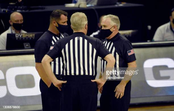 Referees review a call on the court during the Mountain West Conference basketball tournament semifinals between the San Diego State Aztecs and the...