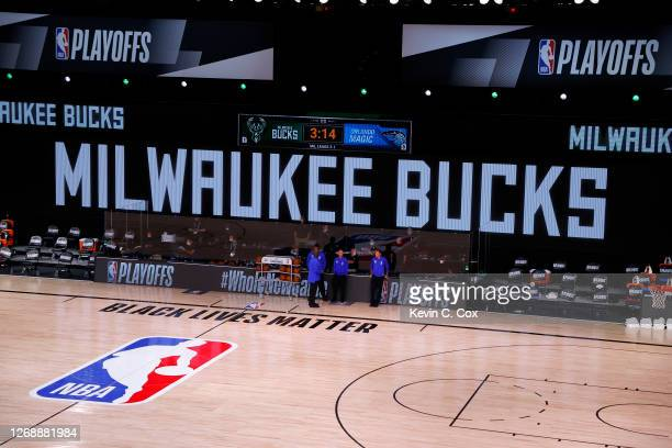 Referees stand on an empty court before the start of a scheduled game between the Milwaukee Bucks and the Orlando Magic for Game Five of the Eastern...