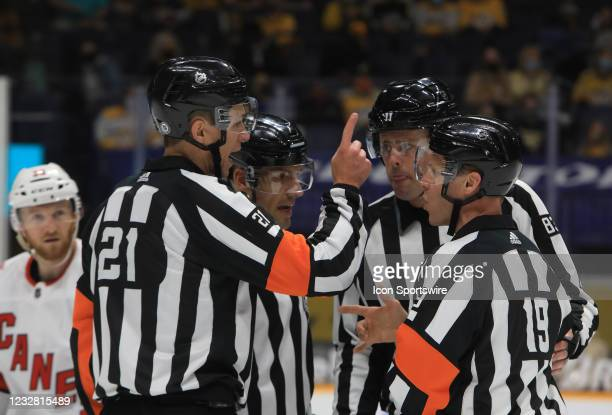 Referees TJ Luxmore and Gord Dwyer and linesmen Matt MacPherson and Bryan Pancich talk during the NHL game between the Nashville Predators and...